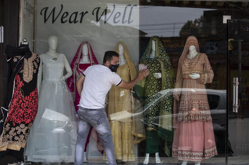 A Kashmiri shopkeeper cleans the display of his shop that was opened following a partial relaxation in the lockdown imposed to curb the spread of coronavirus in Srinagar, Indian controlled Kashmir, Monday, May 31, 2021.