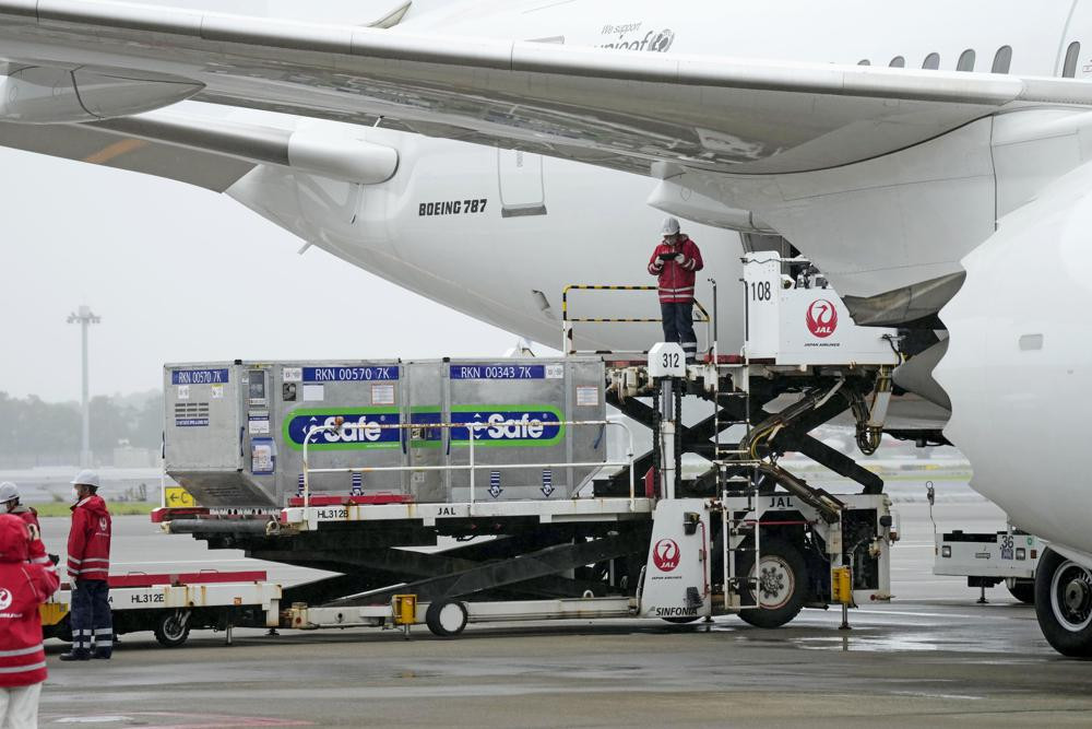 The containers carrying the coronavirus vaccines donated by Japanese government, are loaded to a plane before its departure for Taiwan, at Narita International Airport in Narita, east of Tokyo, Friday, June 4, 2021.
