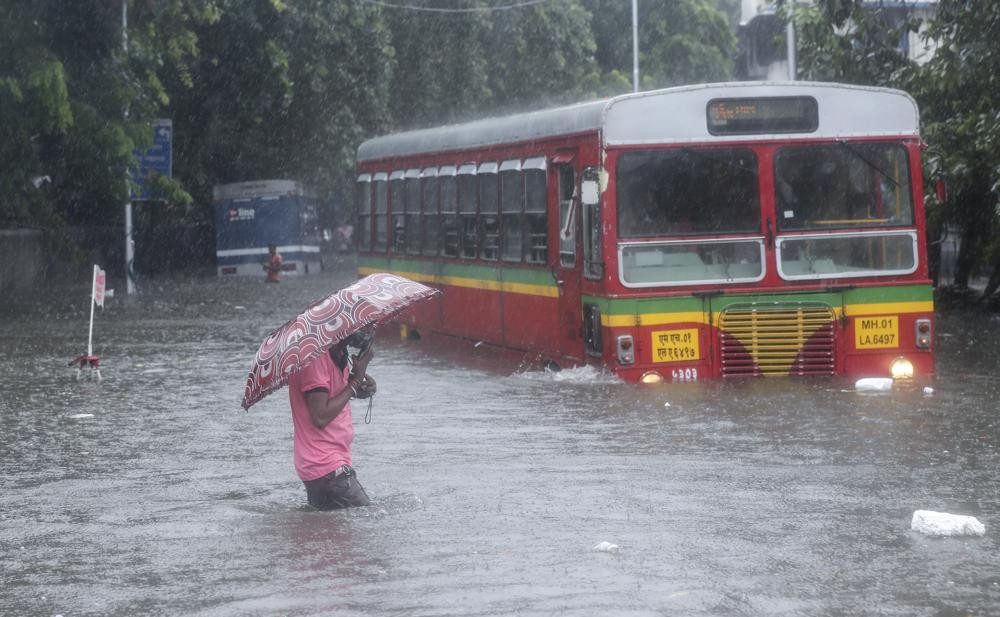 A man makes his way across a flooded street during heavy rains in Mumbai, India, Wednesday, June 9, 2021.