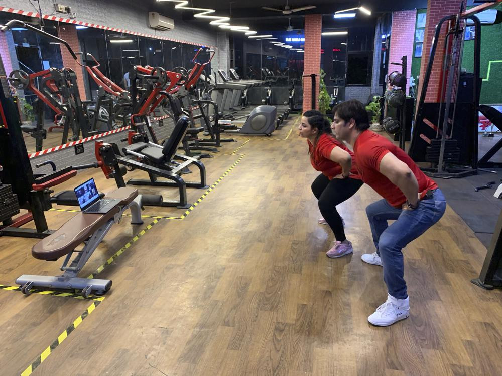 Bijender and Kanika Gautam, owners of the Ultra Bodies Fitness Studio, take online class from their closed Gyms on the outskirts of New Delhi, India, Thursday, June 10, 2021.
