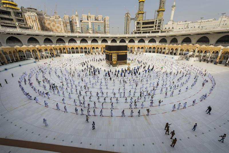 In this July 31, 2020, file photo, pilgrims walk around the Kabba at the Grand Mosque in the Muslim holy city of Mecca, Saudi Arabia.