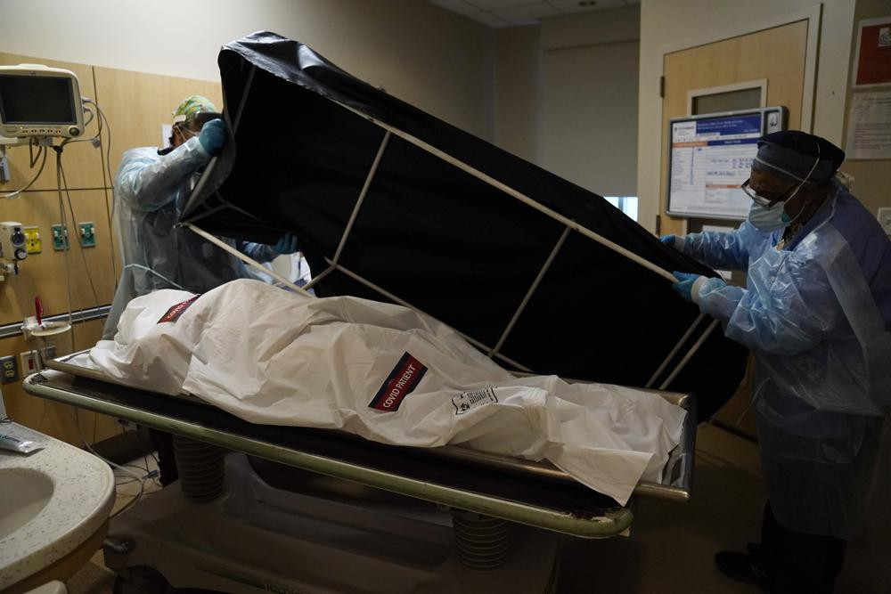 In this Jan. 9, 2021 file photo, transporters Miguel Lopez, right, Noe Meza prepare to move a body of a COVID-19 victim to a morgue at Providence Holy Cross Medical Center in the Mission Hills section of Los Angeles.