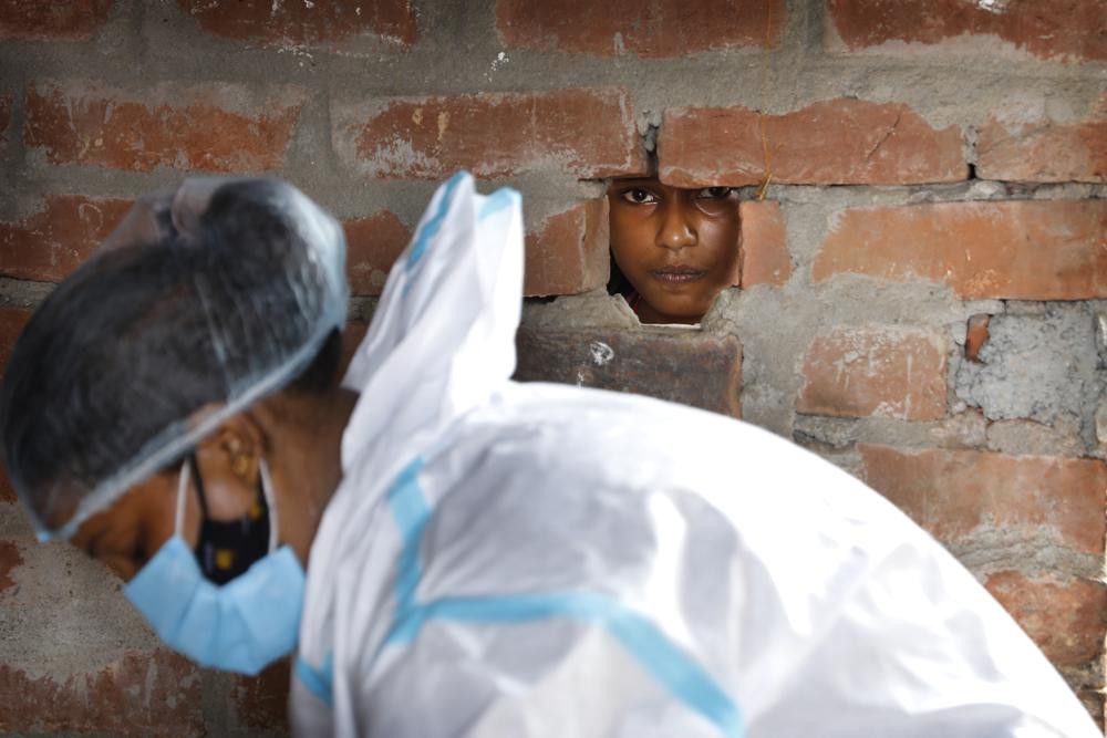 A girl looks out through a hole in the wall of her house as a health worker prepares for COVID-19 testing in Jamsoti village, Uttar Pradesh state, India, on June 9, 2021