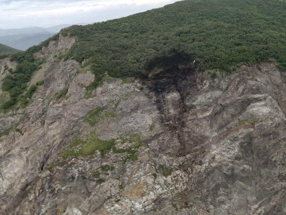 This photo released by the Russia Emergency Situations Ministry press service on Wednesday, July 7, 2021, shows wreckage of a missing Antonov An-26 missing plane found near its destination airport outside the town of Palana, in Russia's Far East.