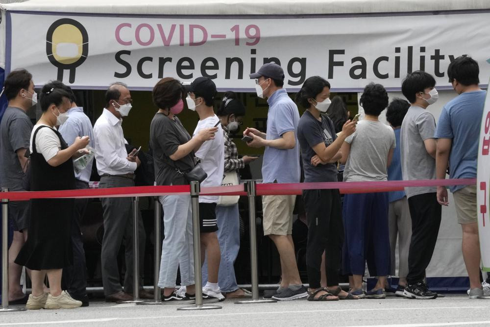 People queue in line to wait for the coronavirus testing at a Public Health Center in Seoul, South Korea, Friday, July 9, 2021.