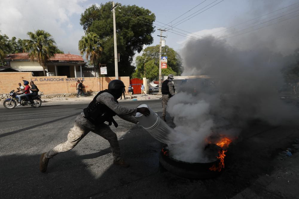 Police put out a burning tire set fire by protesters upset with growing violence in the Lalue neighborhood of Port-au-Prince, Haiti, Wednesday, July 14, 2021.