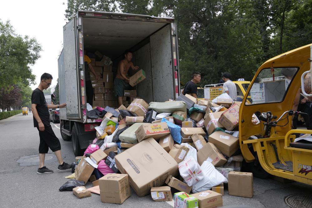 Workers sort out parcels for delivery in Beijing Wednesday, July 14, 2021. China's economic growth slowed to a still-strong 7.9% over a year ago in the three months ending in June as a rebound from the coronavirus leveled off.