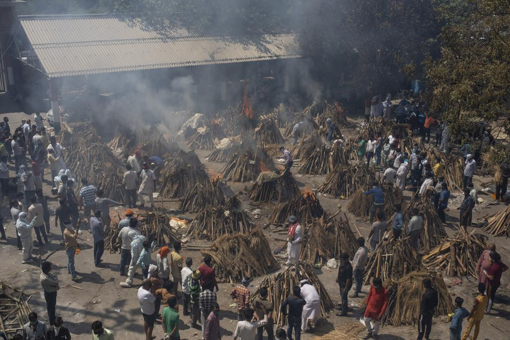 In this April 24, 2021, file photo, multiple funeral pyres of those who died of COVID-19 burn at a ground that has been converted into a crematorium for the mass cremation of coronavirus victims, in New Delhi, India.