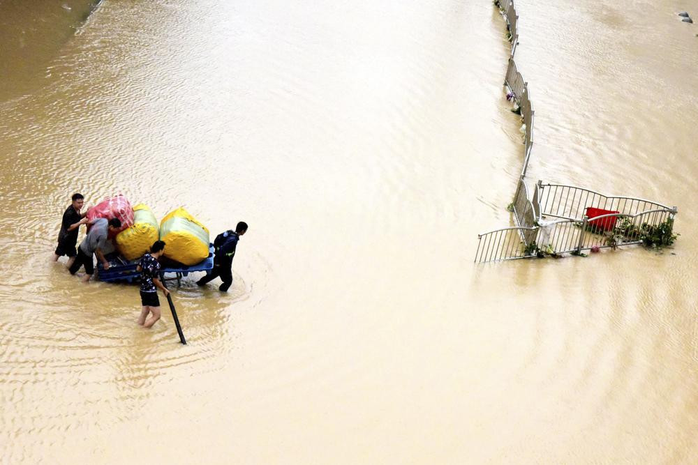 In this photo released by Xinhua News Agency, residents move their belongings across a flooded street in Zhengzhou in central China's Henan province on Wednesday, July 21, 2021.