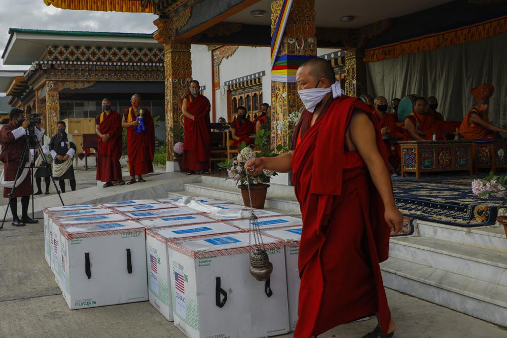 This photograph provided by UNICEF shows monks from Paro's monastic body perform a ritual as 500,000 doses of Moderna COVID-19 vaccine gifted from the United States arrived at Paro International Airport in Bhutan, July 12, 2021.