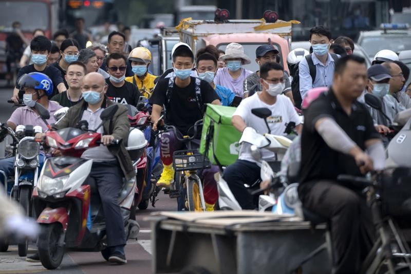 In this file photo dated Friday, July 2, 2021, people riding bicycles and scooters wait to cross an intersection during rush hour in Beijing.