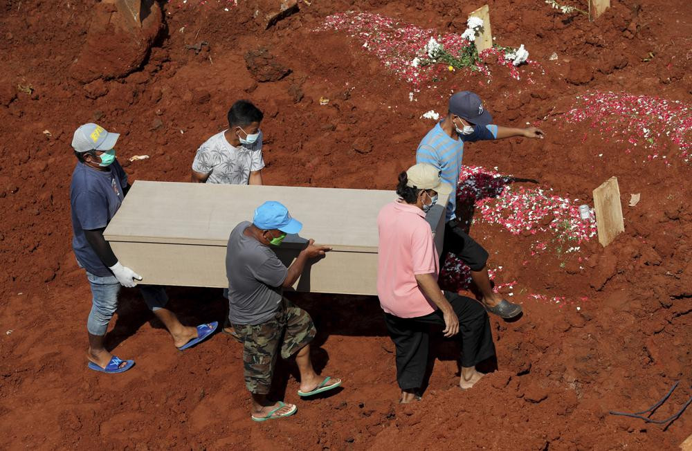 Workers carry a coffin for burial at the special section of Jombang Public Cemetery reserved for those who died of COVID-19, in Tangerang, on the outskirts of Jakarta, Indonesia, Wednesday, Aug. 4, 2021.
