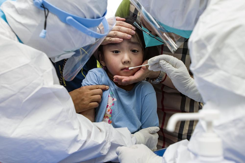 A child reacts to a throat swab during mass testing for COVID-19 in Wuhan in central China's Hubei province Tuesday, Aug. 3, 2021.