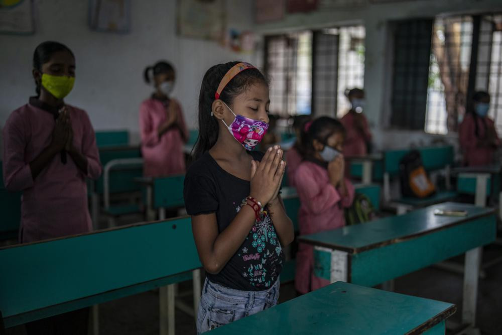 School children attend morning assembly inside a classroom on the first day of partial reopening of schools in Noida, a suburb of New Delhi, India, Wednesday, Sept. 1, 2021.