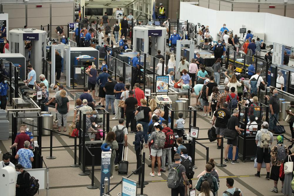 Travelers wear face coverings in the line for the north security checkpoint in the main terminal of Denver International Airport Tuesday, Aug. 24, 2021, in Denver.