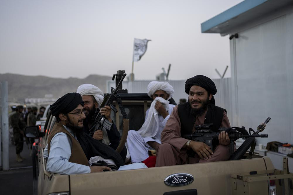 Taliban fighters sit in a pickup truck at the airport in Kabul, Afghanistan, Thursday, Sept. 9, 2021.