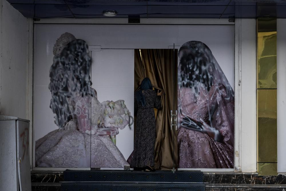 An Afghan woman enters a beauty salon in Kabul, Afghanistan, Saturday, Sept. 11, 2021. Since the Taliban gained control of Kabul, several images depicting women outside beauty salons have been removed or covered up.