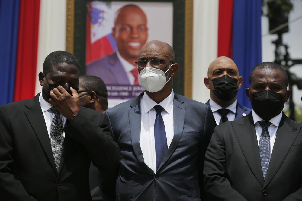 In this July 20, 2021 file photo, Haiti's designated Prime Minister Ariel Henry, center, and interim Prime Minister Claude Joseph, right, pose for a group photo with other authorities in front of a portrait of slain Haitian President Jovenel Moise.