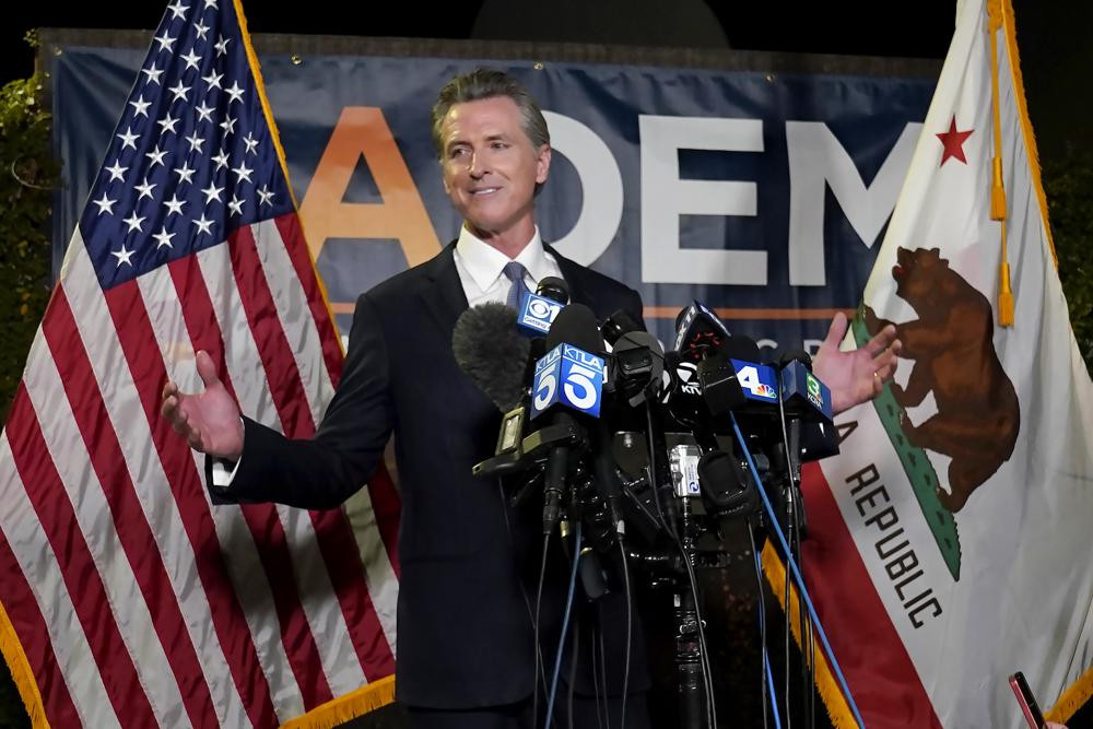 California Gov. Gavin Newsom addresses reporters after beating back the recall attempt that aimed to remove him from office, at the John L. Burton California Democratic Party headquarters in Sacramento, California