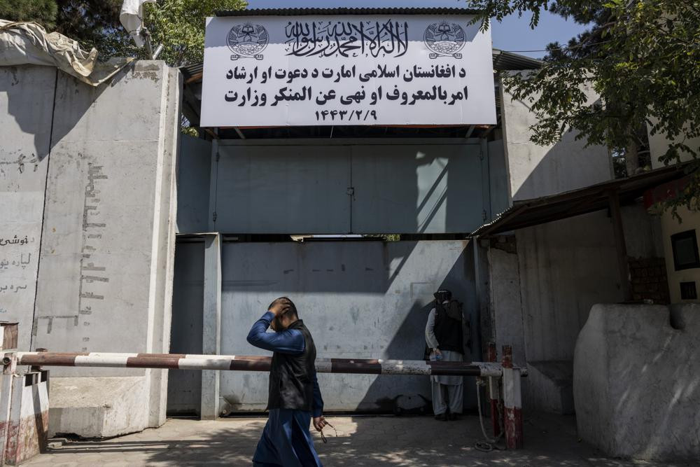 An Afghan man walks past the former Women's Affairs Ministry building in Kabul, Afghanistan, Saturday, Sept. 18, 2021.