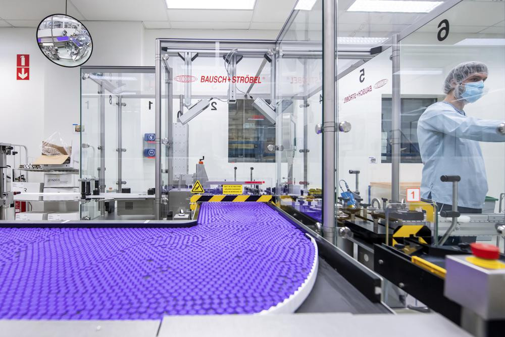 In this March 2021 photo provided by Pfizer, a technician works on a line for packaging preparation for the Pfizer-BioNTech COVID-19 vaccine at the company's facility in Puurs, Belgium.