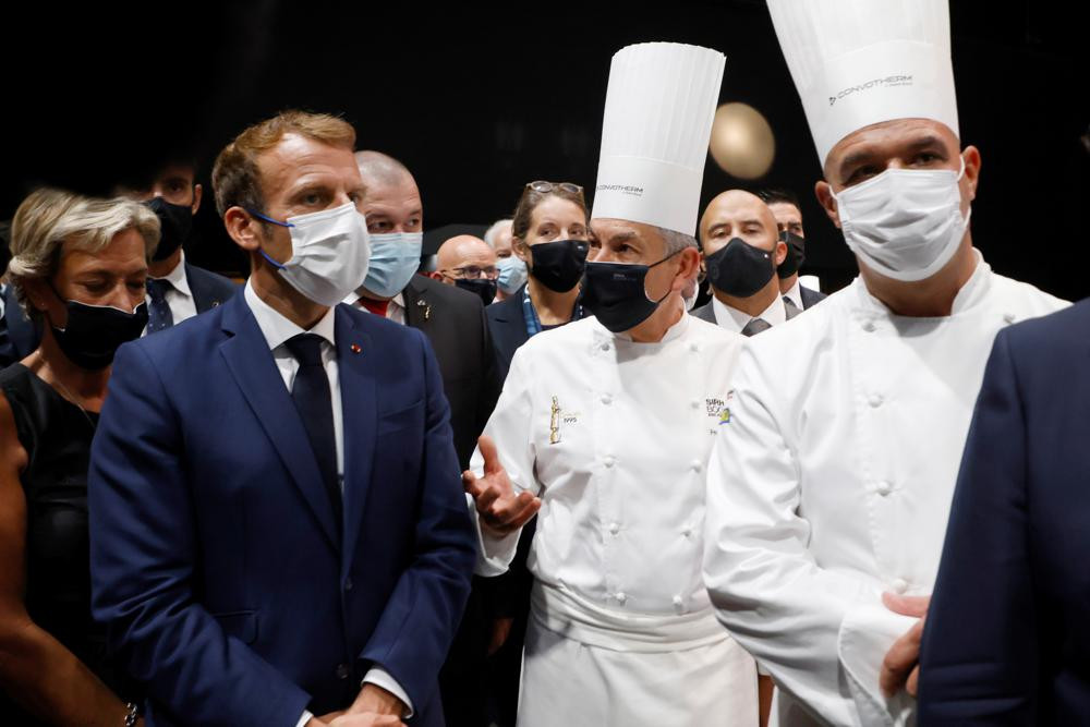 French President Emmanuel Macron, left, speaks with French chefs Regis Marcon, enter, and Jerome Bocuse, right, at the Bocuse d'Or gastronomy contest during the International Catering, Hotel and Food Trade Fair (SIRHA) in Lyon, central France, Monday.