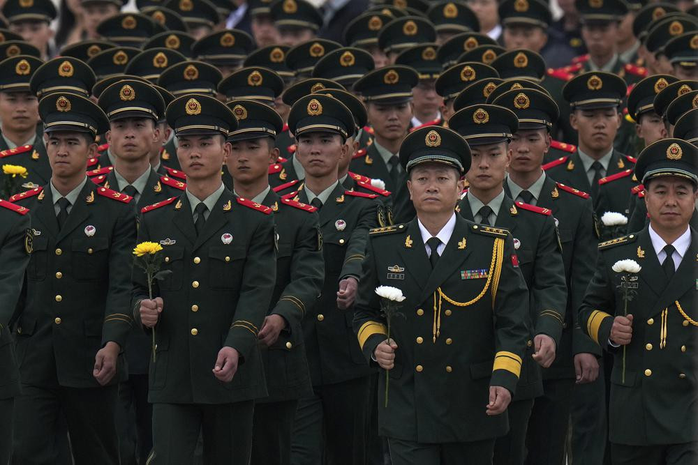 Paramilitary policemen and military officers hold flowers walk to pay respects to the People's Heroes Monument during a ceremony to mark Martyr's Day at Tiananmen Square in Beijing, Thursday, Sept. 30, 2021.