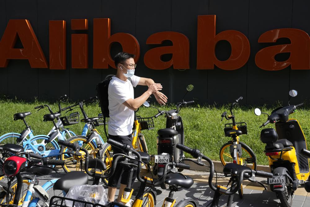 A man passes by the logo for Alibaba outside the Beijing headquarters in Beijing, China, Tuesday, Aug. 24, 2021.