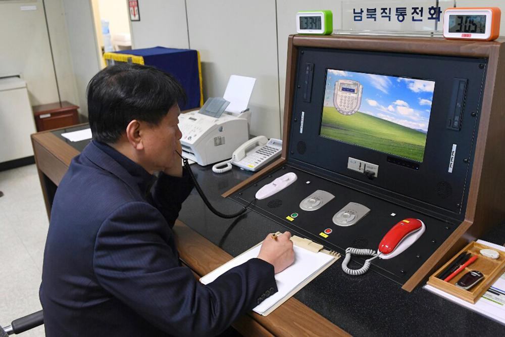 In this Jan. 3, 2018, file photo, a South Korean government official communicates with a North Korean officer during a phone call on the dedicated communications hotline at the border village of Panmunjom in Paju, South Korea.