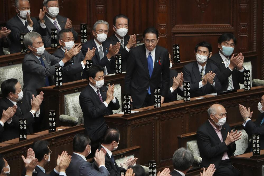 Fumio Kishida, center, is applauded after being elected as Japan's prime minister at the parliament's lower house Monday, Oct. 4, 2021, in Tokyo.
