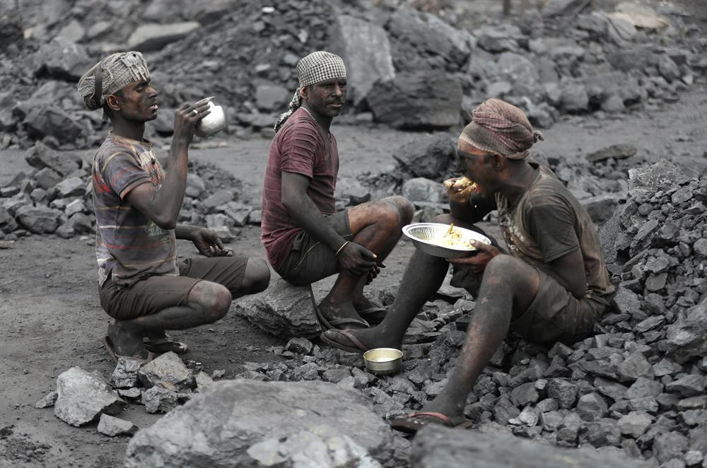 In this Oct. 23, 2019, file photo, laborers eat lunch at a coal loading site in the village of Godhar in Jharia, a remote corner of eastern Jharkhand state, India.