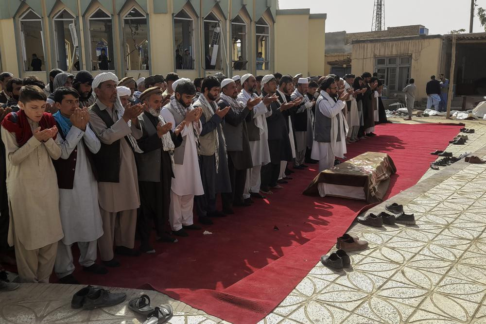 Relatives and residents pray during a funeral ceremony for victims of a suicide attack at the Gozar-e-Sayed Abad Mosque in Kunduz, northern Afghanistan, Saturday, Oct. 9, 2021.