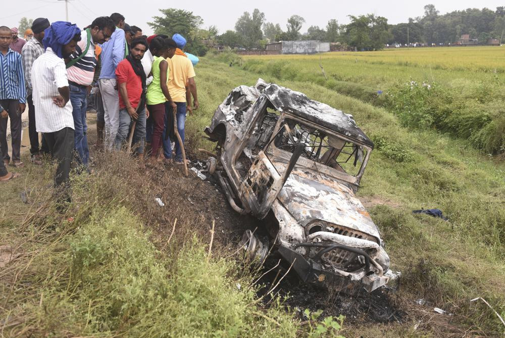 Villagers watch a burnt car which ran over and killed farmers on Sunday, at Tikonia village in Lakhimpur Kheri, Uttar Pradesh state, India, Monday, Oct. 4, 2021.