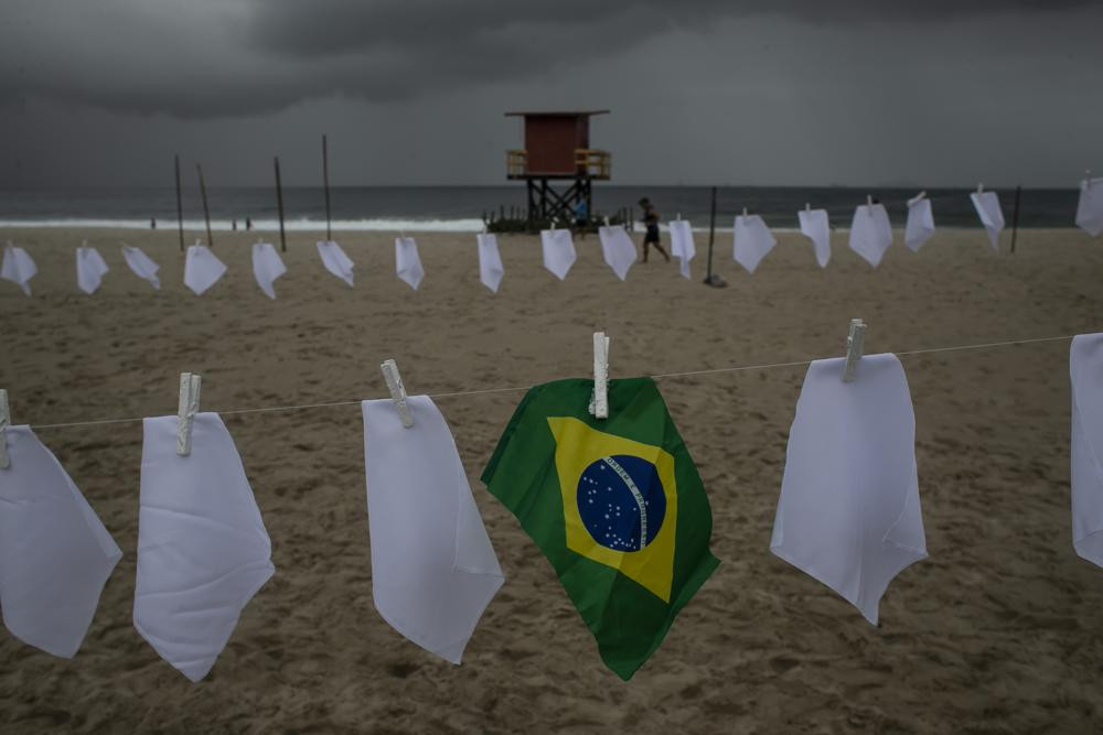 A Brazilian flag hangs on a clothesline on Copacabana beach amid white scarves that represent those who have died of COVID-19 in Rio de Janeiro, Brazil, Friday, Oct. 8, 2021.
