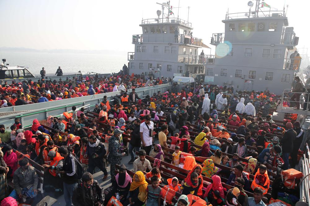 In this Dec. 29, 2020, file photo, Rohingya refugees wait on naval ships to be transported to an isolated island in the Bay of Bengal, in Chittagong, Bangladesh.