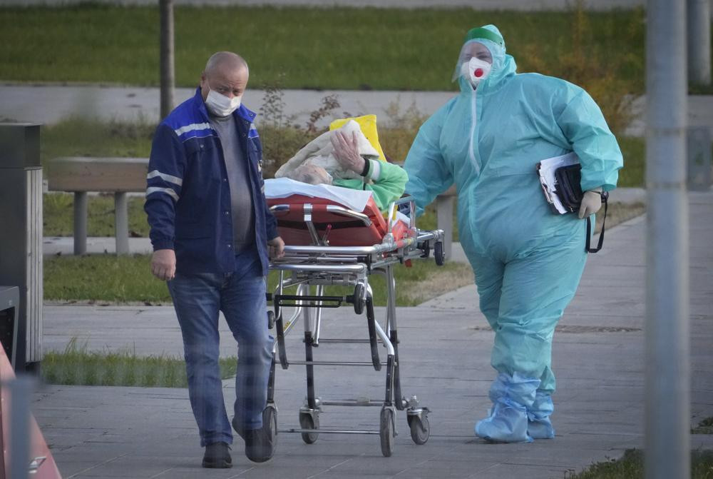 Medical workers carry a patient suspected of having coronavirus on a stretcher at a hospital in Kommunarka, outside Moscow, Russia, Monday, Oct. 11, 2021.