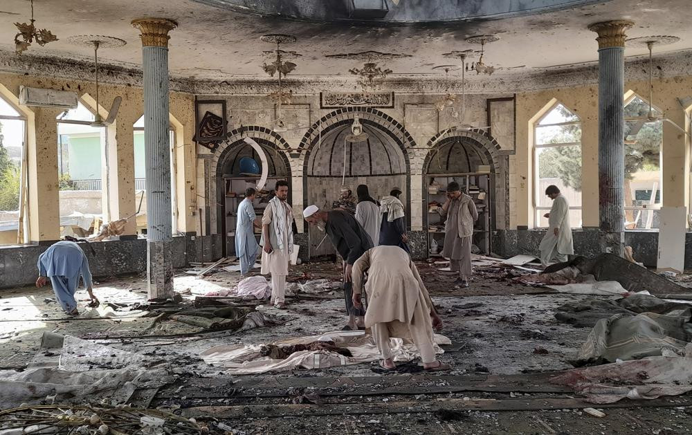 In this Oct. 8, 2021 file photo, people view the damage inside of a mosque frequented by the Shiite Muslim minority following a deadly bombing claimed by the Islamic State that killed dozens, in Kunduz province, northern Afghanistan.