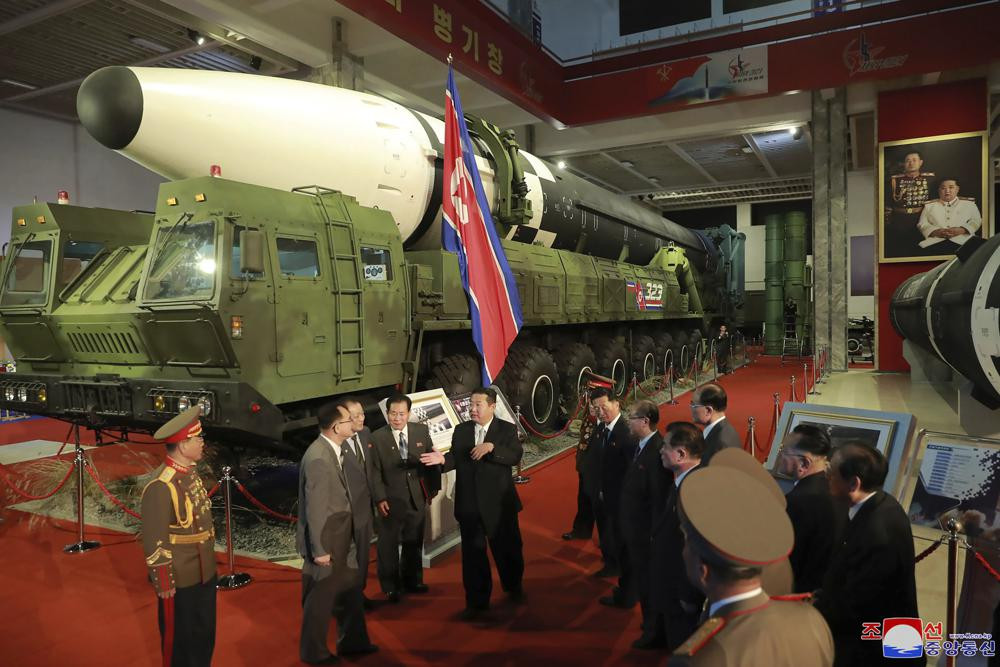 In this photo provided by the North Korean government, North Korean leader Kim Jong Un, center, speaks in front of what the North says an intercontinental ballistic missile displayed at an exhibition of weapons systems in Pyongyang.