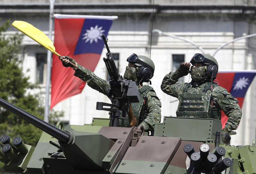 In this Oct. 10, 2021, file photo, Taiwanese soldiers salute during National Day celebrations in front of the Presidential Building in Taipei, Taiwan.