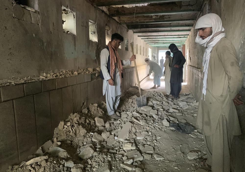People inspect the inside of a mosque following a suicide bombers attack in the city of Kandahar, southwest Afghanistan, Friday, Oct. 15, 2021.