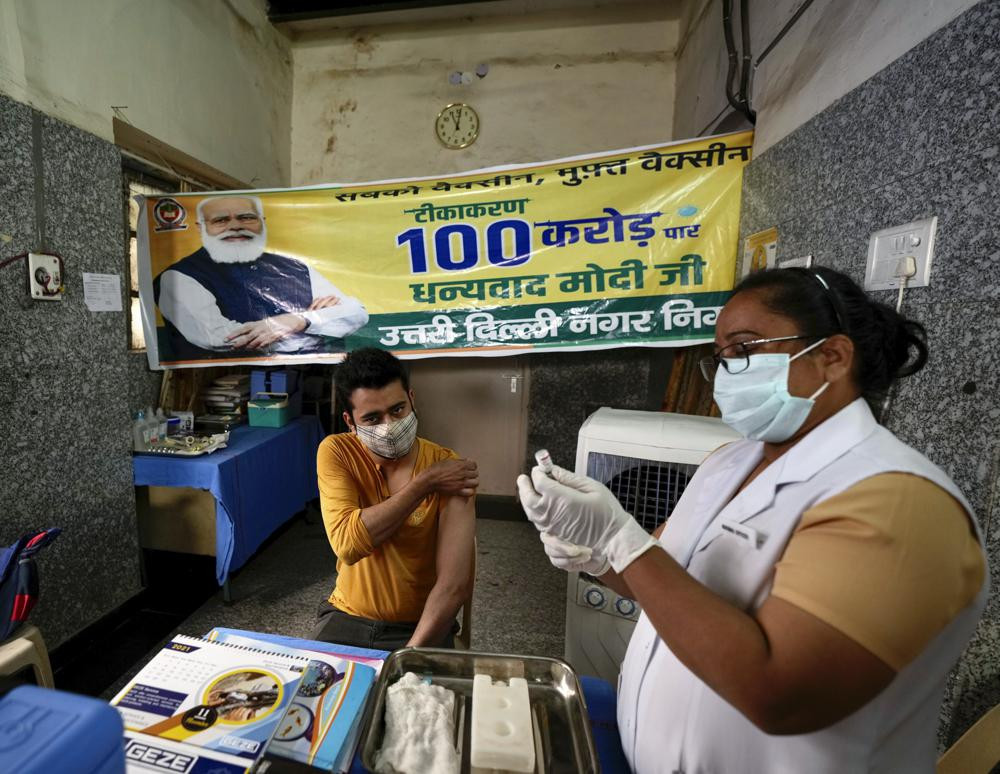 A health worker inoculates a man next to a banner thanking Prime Minister Narendra Modi for 1 billion doses of COVID-19 vaccine at a government hospital in New Delhi, India, Thursday, Oct. 21, 2021.