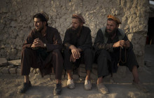 Afghans sit outside a mosque in a poor neighborhood where hundreds of internally displaced people from the eastern part of the country have been living for years, in Kabul, Afghanistan, Monday, Sept. 27, 2021.