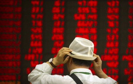 In this Sept. 5, 2019, file photo, an investor adjusts his hat as he monitors stock prices at a brokerage house in Beijing.