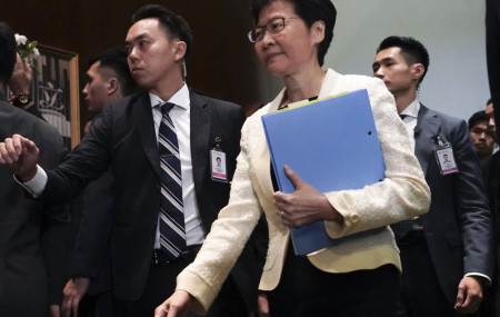 In this Oct. 17, 2019, file photo, Hong Kong Chief Executive Carrie Lam, center, arrives at chamber of the Legislative Council in Hong Kong.