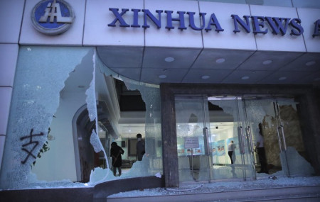 People stand inside the lobby of China's Xinhua News Agency damaged by protesters in Hong Kong, Saturday, Nov. 2, 2019.
