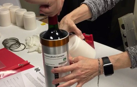 In this Saturday, Nov. 2, 2019 photo provided by Space Cargo Unlimited, researchers with Space Cargo Unlimited prepare bottles of French red wine to be flown aboard a Northrop Grumman capsule from Wallops Island, Va., to the International Space Station.