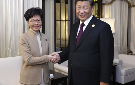 In this Nov. 4, 2019, file photo released by China's Xinhua News Agency, Chinese President Xi Jinping, right, poses with Hong Kong Chief Executive Carrie Lam for a photo during a meeting in Shanghai, China.