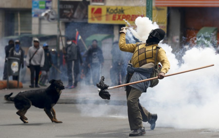 A backer of former President Evo Morales returns a tear gas canister to police during clashes in La Paz, Bolivia, Wednesday, Nov. 13, 2019.