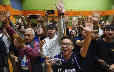 Supporters of pro-democracy candidate Angus Wong celebrate after he won in district council elections in Hong Kong, early Monday, Nov. 25, 2019.