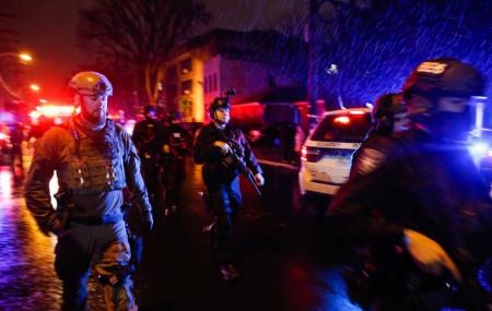 Law enforcement personnel walk near the scene following a shooting, Tuesday, Dec. 10, 2019, in Jersey City, N.J.